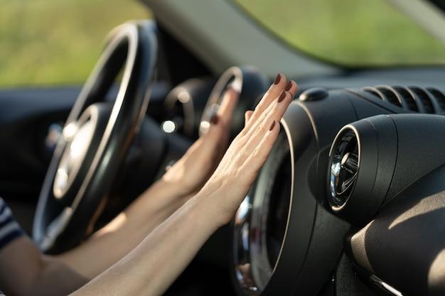 車の熱と自動車のクーラーのエアコングリッドからの冷却空気の打撃で女性ドライバーの手