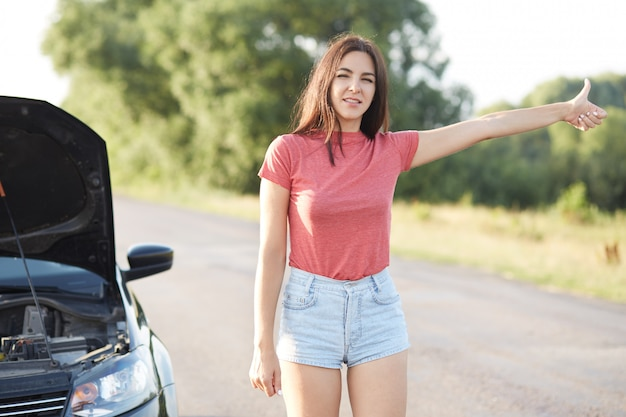 Female driver hitchhikes on road, asks for help in other drivers, has brocken car, doesn`t know how repair it