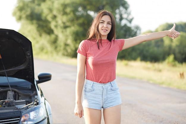 L'autista femminile fa l'autostop su strada, chiede aiuto in altri conducenti, ha rotto l'auto, non sa come ripararla