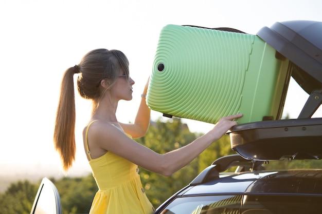 Водитель-женщина в летнем платье кладет зеленый чемодан в багажник на крыше своего автомобиля. концепция путешествий и каникул.