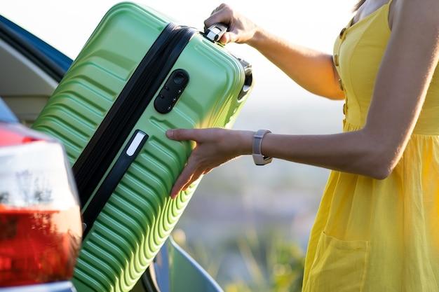 그녀의 차 트렁크 안에 녹색 가방을 넣어 여름 드레스에 여성 드라이버. 여행 및 휴가 개념입니다.