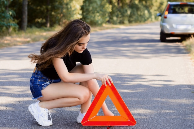Female driver places emergency sign triangle near the car to warn other drivers about the car incident