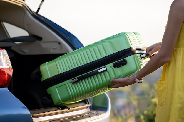 Female driver putting green suitcase inside her car trunk. travel and vacations concept.