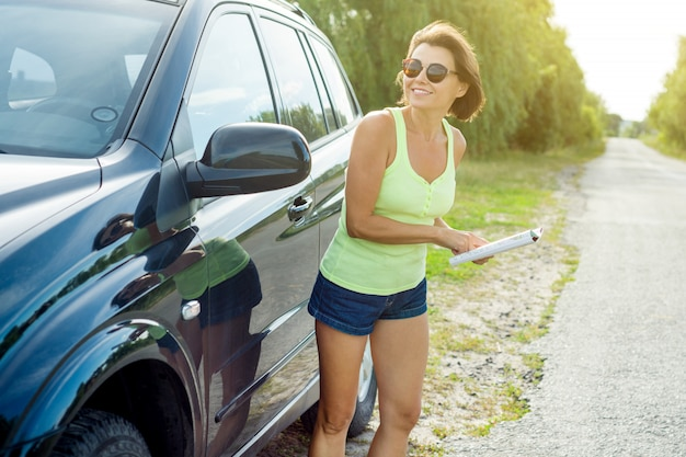 Female driver reading map near a car