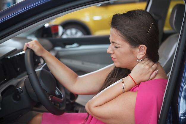 車に座って、彼女の傷ついた首をこすりながら女性ドライバー