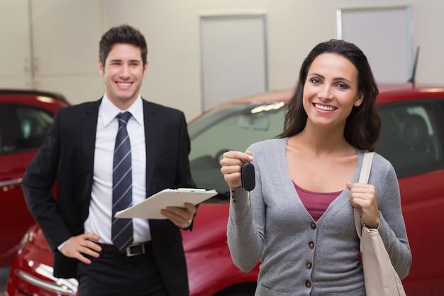 Женский водитель показывает ключ после того, как новый автомобиль