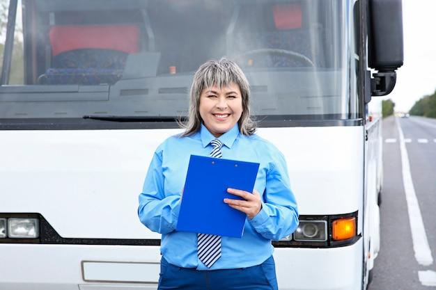 バスの前に立っている女性ドライバー