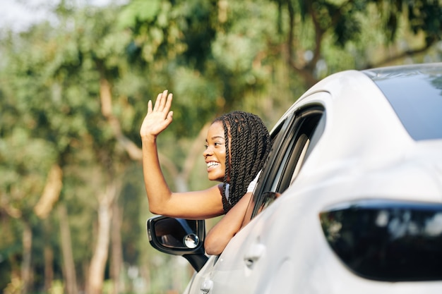Female driver waving friend