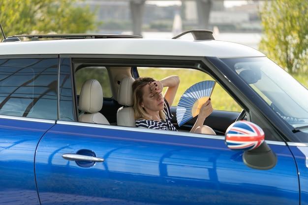 Женщина-водитель с ручным вентилятором, страдающая от жары в машине, имеет проблему с неработающим кондиционером