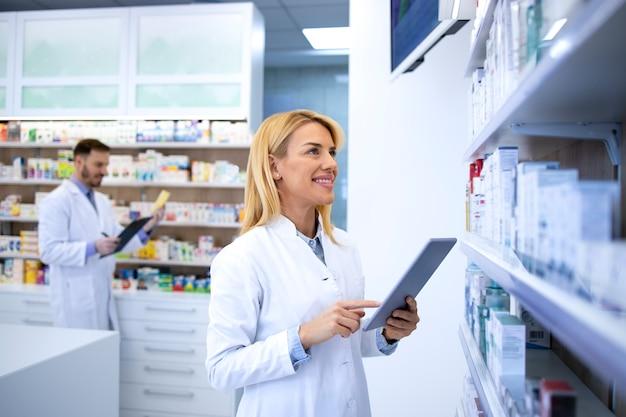 Женский аптекарь проверяет лекарства на полке в аптеке.
