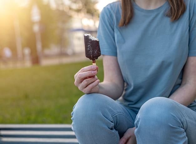 Женщина ест мороженое в летнем парке крупным планом