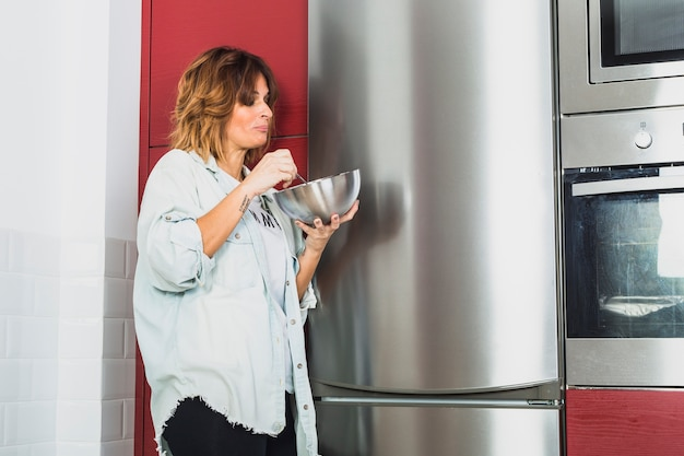 Female eating standing near kitchen appliances