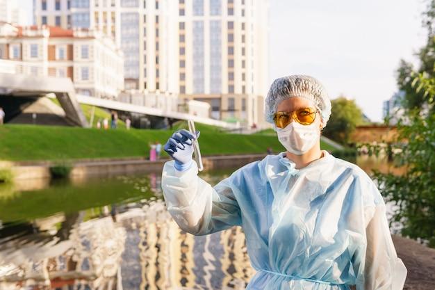 市の川からの水で試験管を保持している保護マスクの女性の生態学者