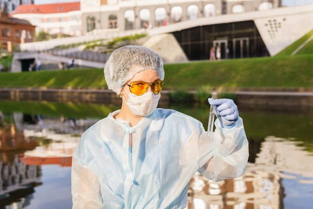 市の川からの水でテストを保持している保護マスクの女性の生態学者