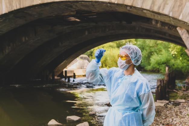 女性の生態学者または疫学者が古い橋の下の都市の川で試験管の水分析を行います