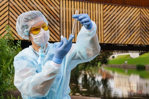 女性の生態学者または疫学者は、都市の水路の水質を視覚的に評価します