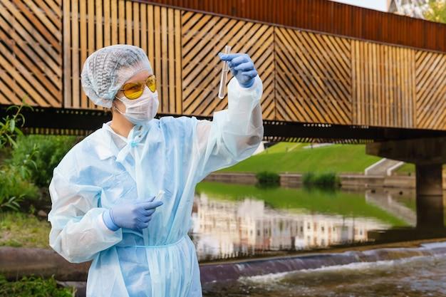 女性の生態学者または疫学者は、都市の川の水質を視覚的に評価します