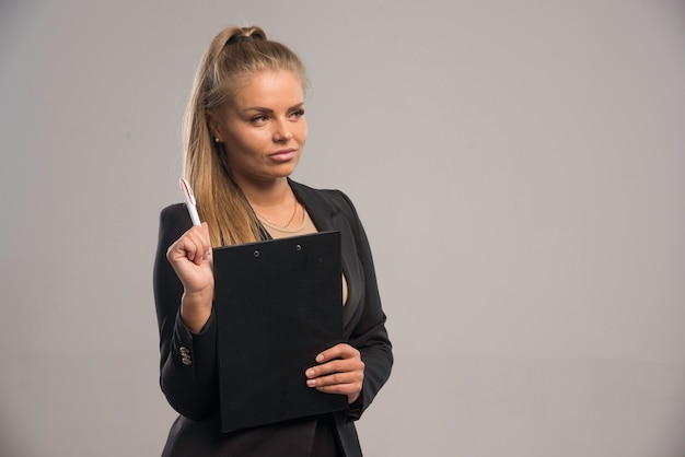 Female employee in black suit holding a contract and looks doubtful.