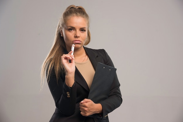 Impiegato femminile in vestito nero che tiene un contratto e sembra premuroso.