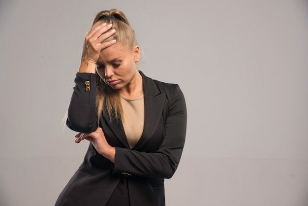 Female employee in black suit looks bored.