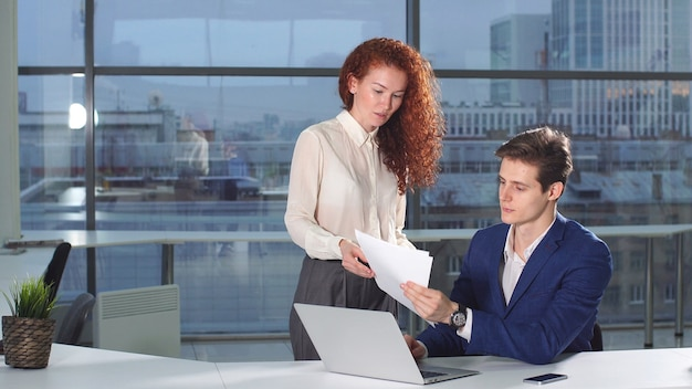 Female employee of the company brings financial documents to his boss