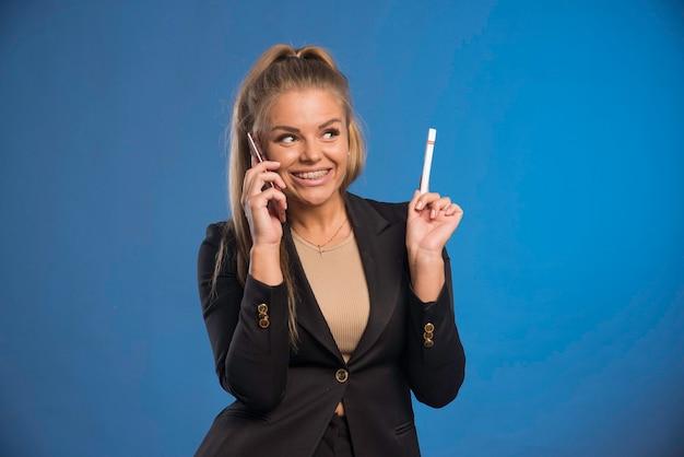 Сотрудница-женщина разговаривает по телефону, держа ручку и смеясь.