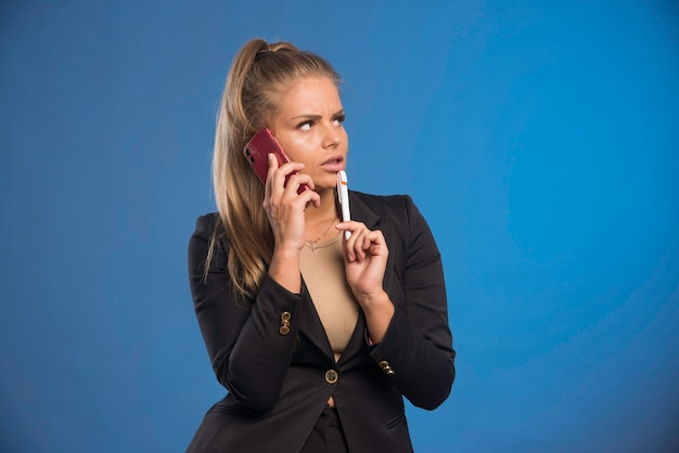 Female employee having phone talk while holding a pen and looks doubtful.