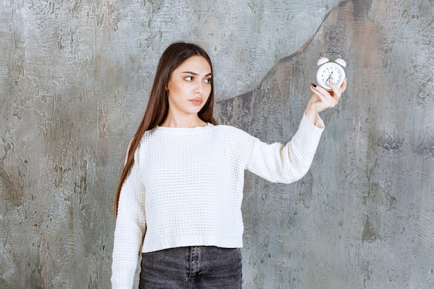 Female employee holding an alarm clock on concrete wall.