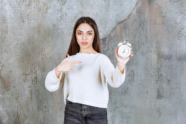 콘크리트 벽에 알람 시계를 들고 여성 직원.