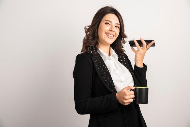Impiegata che tiene tazza di tè e telefono