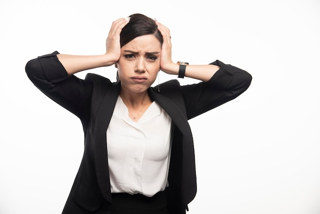 Female employee holding her head on white background. high quality photo