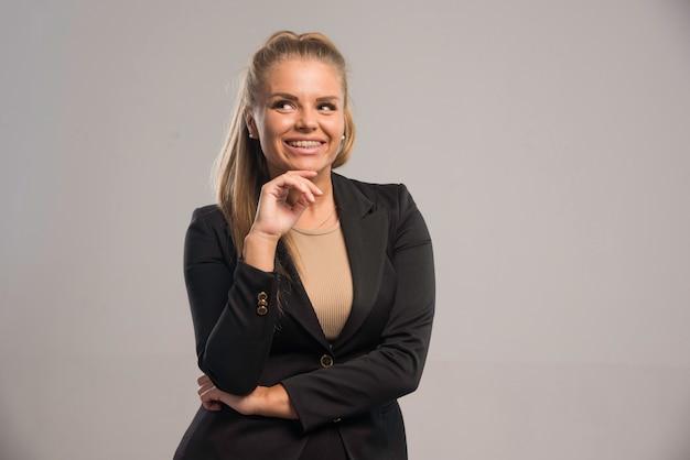 검은 양복을 입은 여성 직원이 긍정적으로 보입니다.