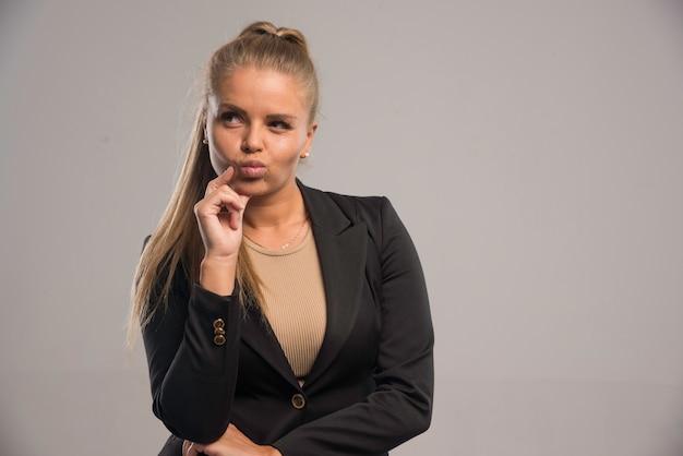 黒のスーツを着た女性社員は後悔しているようです。