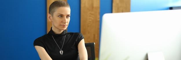 Сотрудница в стильной одежде сидит в офисе перед монитором компьютера