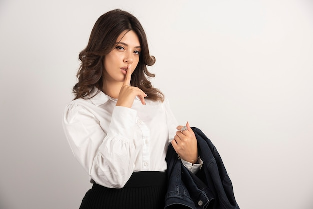 白で沈黙のサインを作る女性従業員。