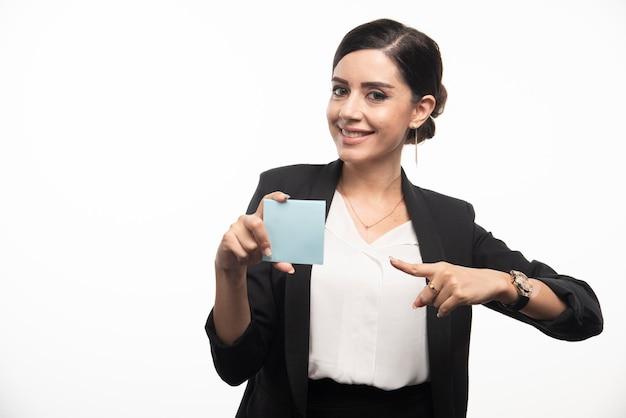 白い背景にメモ帳を指差す女性社員。高品質の写真