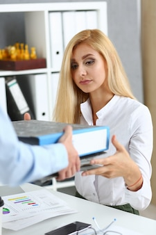 Female employee show pack of documents to busy