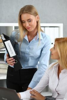 Сотрудница показывает пакет документов занятому