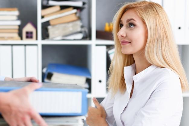 Сотрудница показывает пакет документов менеджеру