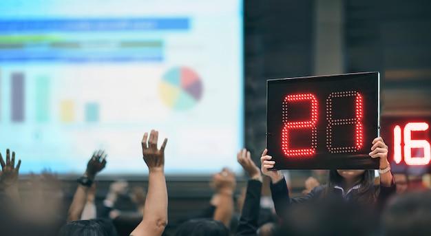 Сотрудник женского пола показывает цифровое табло во время собрания голосования.