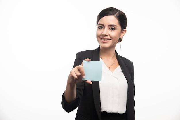 흰색 바탕에 메모 패드를 보여주는 여성 직원. 고품질 사진