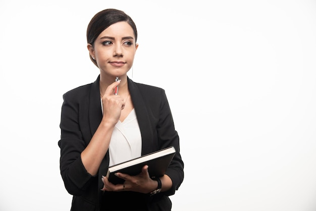 Impiegata femminile con libro pensando al prossimo progetto. foto di alta qualità