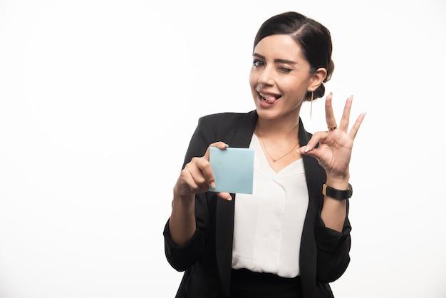 白い背景に顔を作るメモ帳を持つ女性社員。高品質の写真