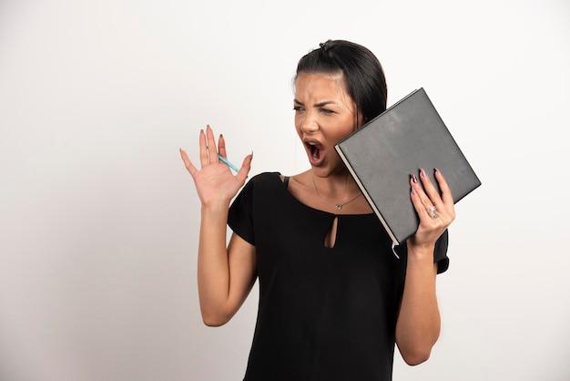 白い壁に叫んでいるノートを持つ女性従業員。