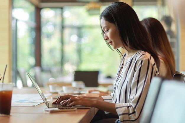 Сотрудник женского пола, работающий и сосредоточенный на ноутбуке в офисной комнате с коллегой