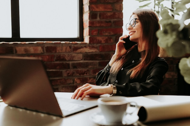 Работница работает в офисе с помощью телефона и компьютера