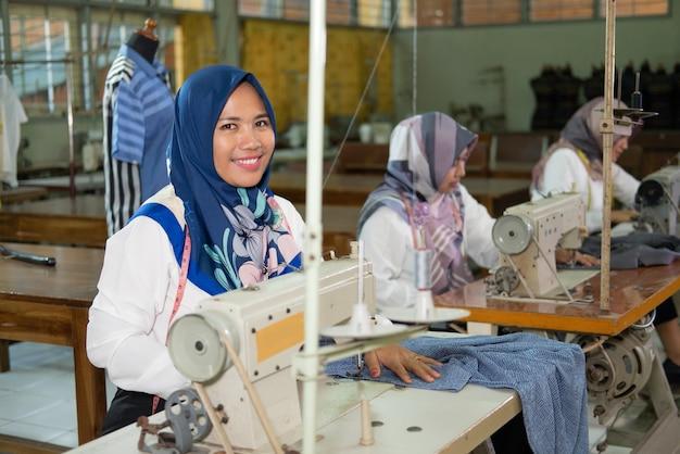 スカーフの女性従業員がミシンで作業しながらカメラを見て微笑む