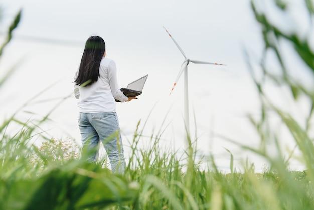 Женщина-инженер ветряной электростанции работает на ноутбуке