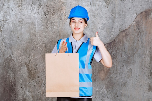 Female engineer in blue helmet and gear holding a cardboard shopping bag and showing thumb up.