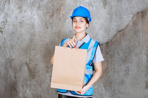 Female engineer in blue helmet and gear holding a cardboard shopping bag.